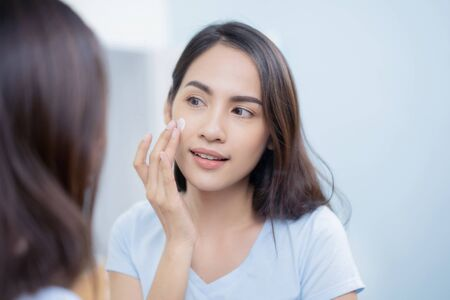 Photo pour Asian women applying face lotion. - image libre de droit