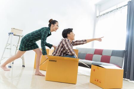 Photo pour Asian couples are moving home. He is fun to move the box. - image libre de droit