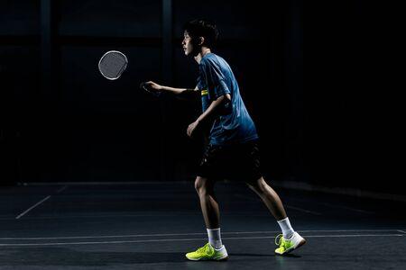 Photo pour Asian badminton player is hitting in court - image libre de droit