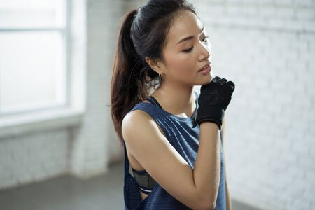 Foto de Asian girl exercising in gym she tired and She has sweat on her face. - Imagen libre de derechos