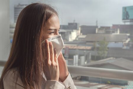 Asian woman  going to work.she wears N95 mask.prevent PM2.5 dust and smog