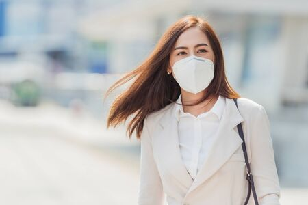 Photo pour Asian woman  going to work.she wears N95 mask.Prevent PM2.5 dust and smog - image libre de droit