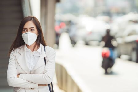 Photo pour Asian woman are going to work.she wears N95 mask.prevent PM2.5 dust and smog. - image libre de droit