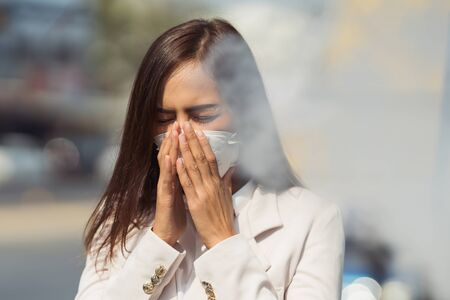Foto per Asian woman are going to work.she wears N95 mask.prevent PM2.5 dust and smog.she is coughing - Immagine Royalty Free