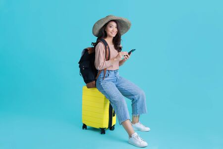Photo pour Asian women tourists she is sitting at the airport. She uses a mobile phone. - image libre de droit