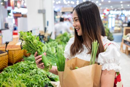 Photo pour Asian woman buy vegetables in the supermarket. She uses paper bags and woven bags. For the environment - image libre de droit