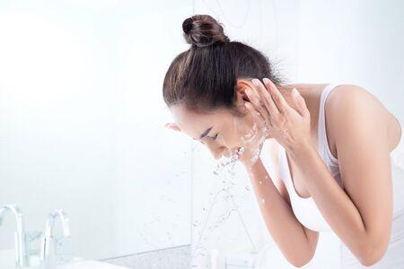 Foto de Asian woman washing face in the bathroom - Imagen libre de derechos