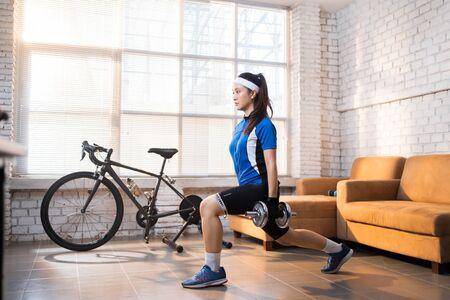 Foto de Cyclist exercise with Leg lunges. She's at home. - Imagen libre de derechos
