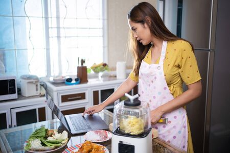 Photo pour Asian woman Cooking in the kitchen She looks at how to make from a laptop. - image libre de droit