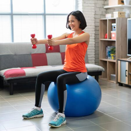Photo pour Beautiful asian woman Use dumbbell exercises at home She is sitting on the ball - image libre de droit