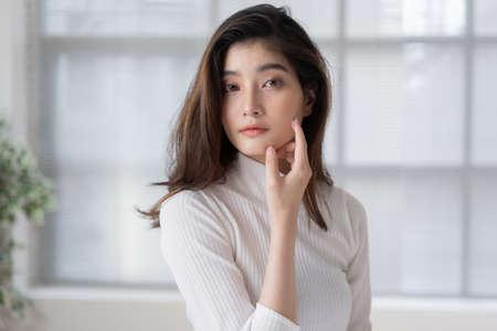 Photo pour Asian woman is applying cream to her face. - image libre de droit