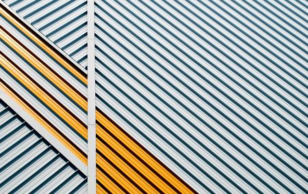 yellow and white striped facade with a geometrical pattern