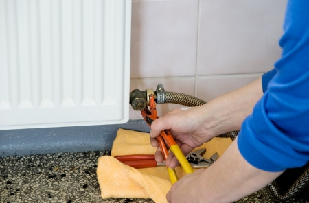 hands of a plumber repairing a gas heating