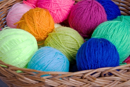 colorful balls of wool in a knitting basket