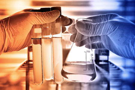Photo pour Flask in scientist hand with laboratory glassware background - image libre de droit