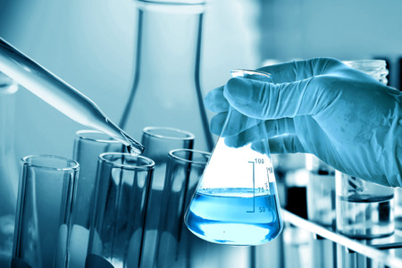 Flask in scientist hand with laboratory glassware background