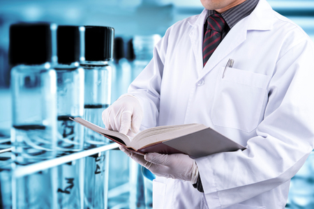 Doctor read textbook with lab background