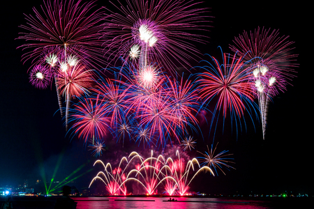 Photo pour Amazing colorful fireworks display for celebration night on the sea with blur city night background. Celebrate on Christmas and countdown to happy new year concept. - image libre de droit