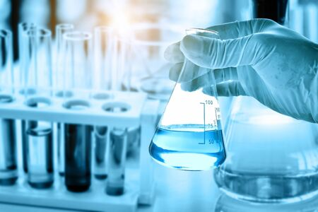 Foto für hand of scientist holding flask with lab glassware in chemical laboratory background, science laboratory research and development concept - Lizenzfreies Bild