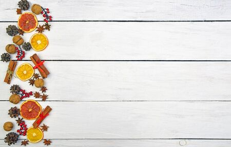 Photo pour  long Christmas ornament made of gingerbread, cones, cinnamon, nuts, anise stars, dried fruits on a wooden background. Christmas background in a rustic style. Top view. Home cosiness. Food background. - image libre de droit