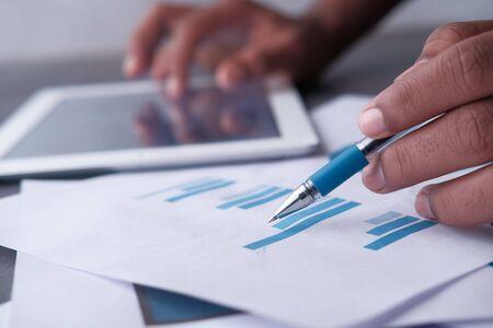 Photo pour Close up of man analyzing bar chart on paper - image libre de droit
