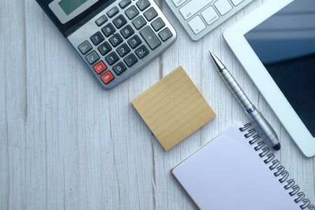 Photo pour top view of digital tablet , calculator and notepad on white background . - image libre de droit