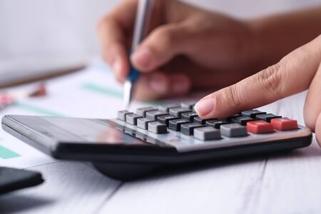 Photo pour Woman accountant or banker use calculator on table at office - image libre de droit