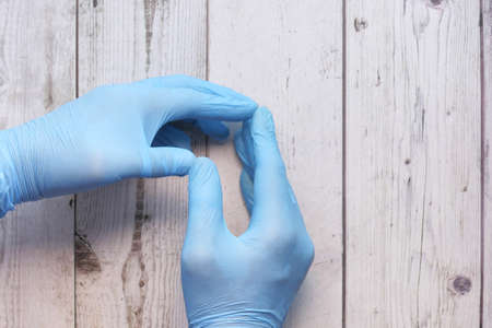 Photo pour Doctor hand with glove on wooden background. - image libre de droit
