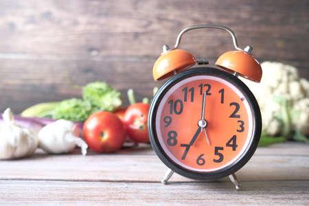 Foto de alarm clock and fresh vegetables on table with copy space - Imagen libre de derechos