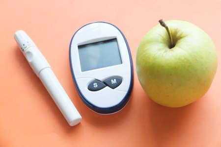 Photo pour diabetic measurement tools, apple on orange background - image libre de droit