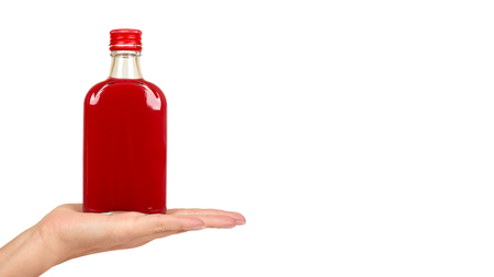 Glass bottle with red tincture in hand isolated on white background. Alcohol problem. copy space, template.