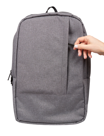 Photo pour Hand with gray textile school bag, city street backpack. Isolated on white gackground - image libre de droit