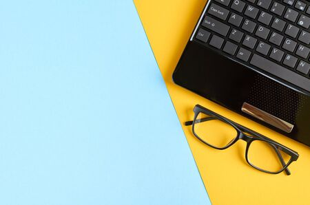 Photo for Black glasses and laptop keyboard on blue and yellow background composition. Flat lay and top view photo - Royalty Free Image