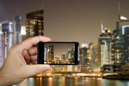 Hand and cellphone with modern buildings in Dubai