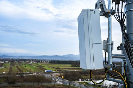 Photo pour 5G new radio telecommunication network antenna mounted on a metal pole providing strong signal waves from the top of the roof across big city - image libre de droit