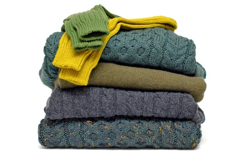 Stack of chunky Irish wool cable knit, Cashmere and Aran winter men's sweaters in fall and winter colours against white