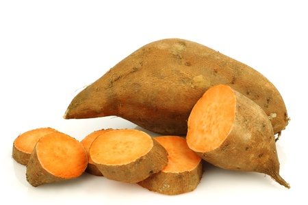 one whole sweet potato and a cut one on a white background