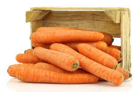 fresh winter carrots coming from a wooden box on a white background