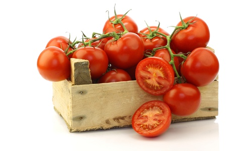 fresh tomatoes on the vine and a cut one in a wooden crate on a white background