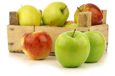 assorted fresh apples in a wooden crate on a white background