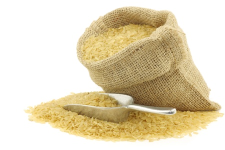 unpolished rice  whole grain  in a burlap bag with an aluminum scoop on a white background