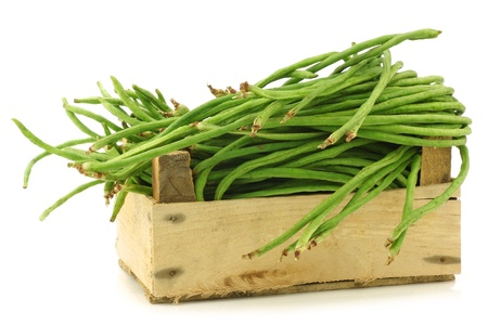 fresh long beans Vigna unguiculata subsp  sesquipedalis  in a wooden crate on a white background