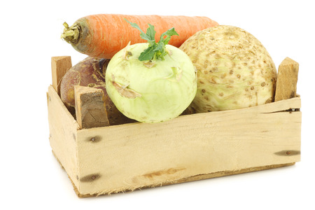 mixed cabbage and root vegetables in a wooden crate on a white backgroundの写真素材