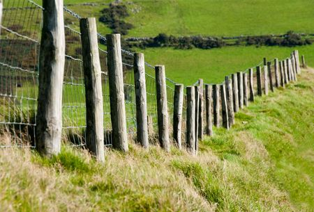 Wodded post with Metal Wire Fence Running through a Grass Field for Cattle