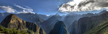 View of Andes Mountain Range from Machu Picchu. Beautiful scenery with Sun Rays shining through the Mountains Peaks