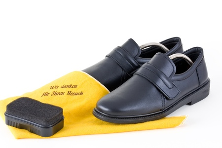 Shoes for men with cleaning cloth and sponge on a white background into.