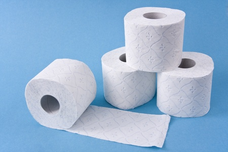 Four toilet paper rolls three of them to build a pyramid shown on light blue background.