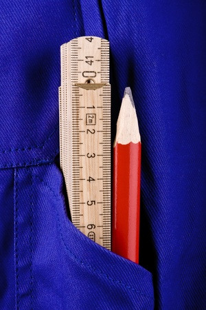 A ruler and a red pencil in the pocket of a blue work pants.