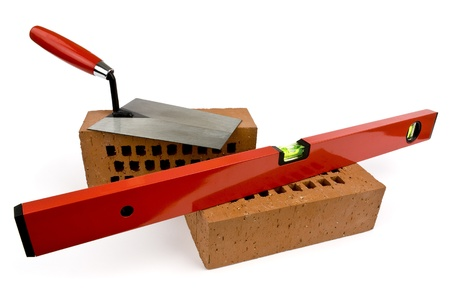 Bricks, level and trowel on a white background shown.