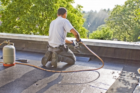 A roofer with a gas burner is kneeling on a roof, and heated a piece of roofing felt